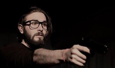 Un actor finge apuntar a alguien con una pistola