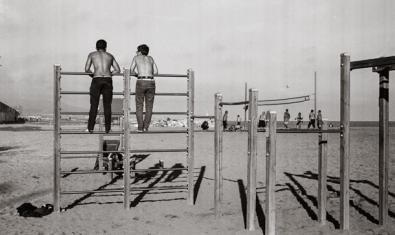 Una de les imatges de l'exposició mostra dos nois d'esquenes a la platja de la Barceloneta