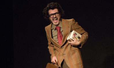 Marc Rodrigo con gafas un traje llamativo y un montón de libros bajo el brazo