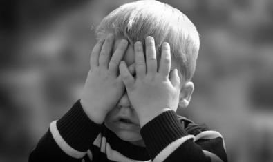 Nen tapant-se la cara amb les mans, blanc i negre.