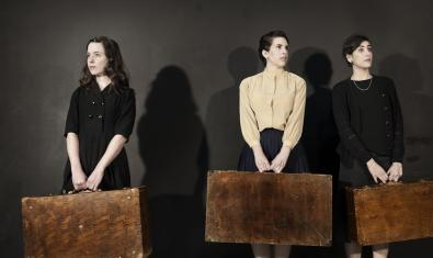Les tres protagonistes de l'espectacle retratades a l'escenari portant una gran maleta cadascuna