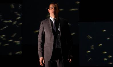 El protagonista del montaje con americana y corbata de pie en el centro de un escenario a oscuras