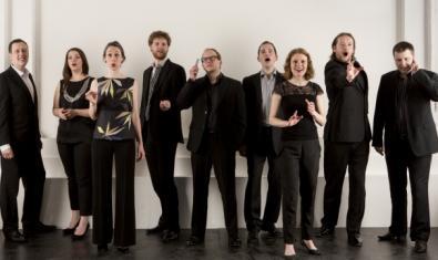 Els integrants de l'ensemble vocal cantant drets vestits de negre i amb una paret blanca al fons