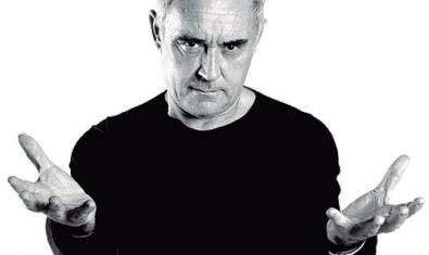 Ferran Adrià with his hands open, looking at the camera. Black and white photograph.