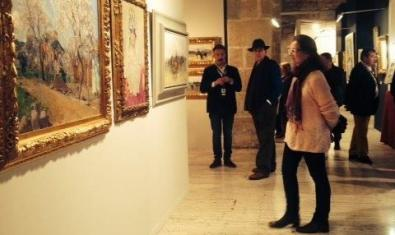 People looking at paintings in a gallery.