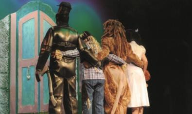 Fotografia dels quatre protagonistes d'esquena a l'escenari, a punt d'entrar a la porta màgica.