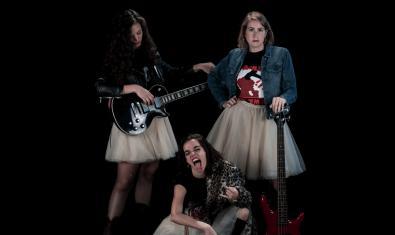 Las tres protagonistas vestidas con falda de tul con guitarras eléctricas en la mano y un ademán desvergonzado propio de estrellas del rock