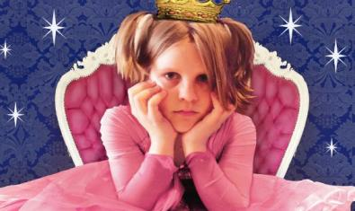 A girl dressed as a princess, all in pink, seated on a pink throne.