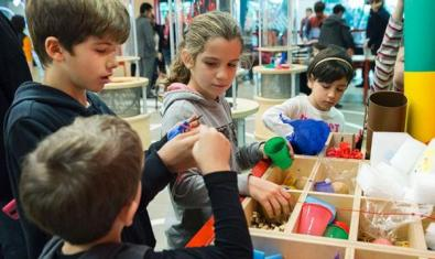 Nens de diferents edats buscant en un calaix molt gran ple de diversos materials.