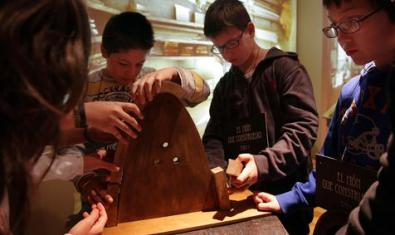 Children around a table making a wooden figure.