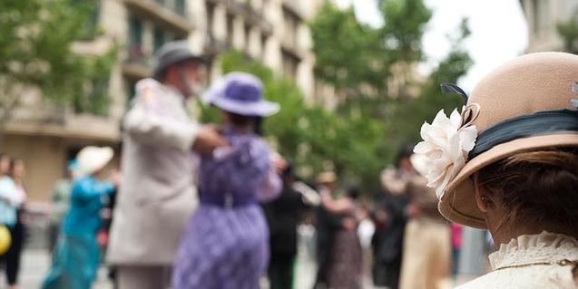 Una dona d'esquena i altres persones vestides com a l'època modernista
