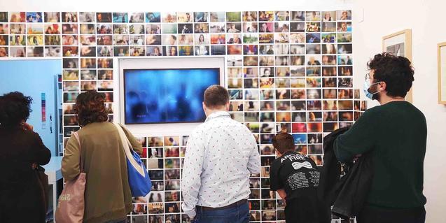 Un grup de visitants es mira les imatges de la mostra el dia de la inauguració
