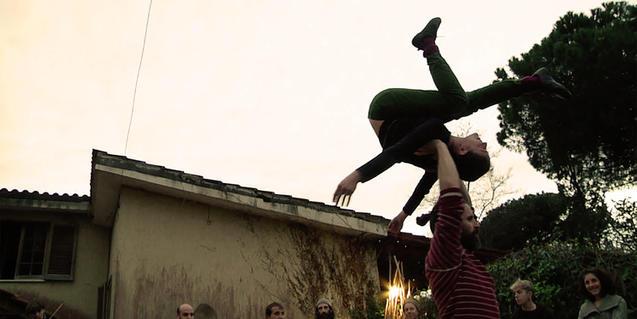 La imagen de una artista haciendo una voltereta en el aire mientras un compañero la sujeta sirve para anunciar el espectáculo