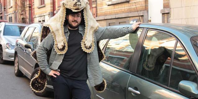 El creador del espectáculo con una piel de animal en la cabeza y apoyado en un coche