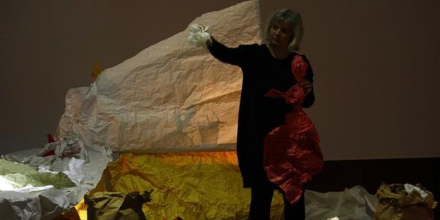 Núria Mestres en el escenario jugando con la luz y los papeles