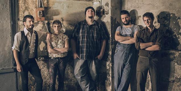 Los cinco integrantes de la banda, fotografiados en un espacio industrial