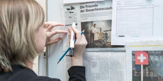 Una mujer manipula unos recortes de periódico colgados en la pared
