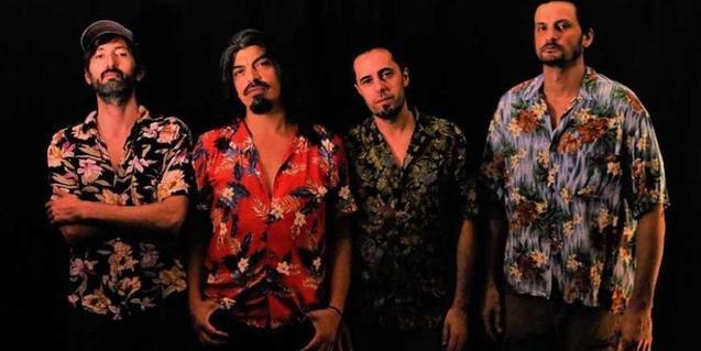 Els quatre integrants de la formació retratats amb camises de flors sobre un fons negre