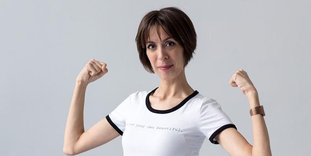 Retrato de la monologuista mostrando al público sus bíceps cómo si fuera una gimnasta