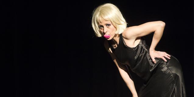 Una ballarina amb vestit de nit i un xumet a la boca durant la representació
