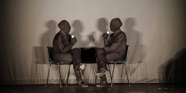 Dos intérpretes con el cuerpo y la cara cubiertos por una tela negra, sentados con un micro en la mano