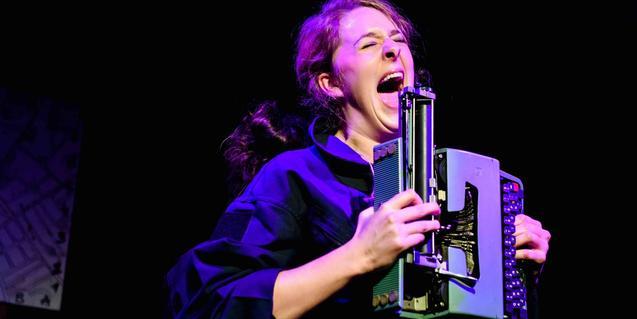 Una de les actrius a l'escenari cridant amb una màquina d'escriure.