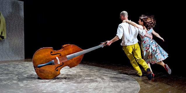 Fotografia de l'espectacle es veuen els dos actors ballant amb un contrabaix