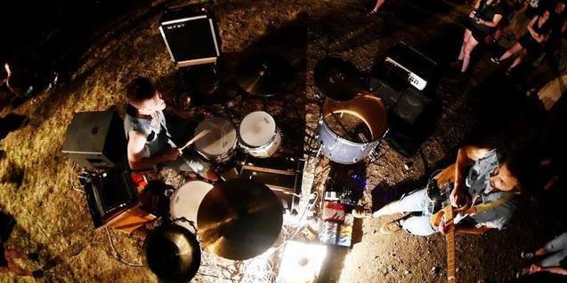 Los músicos de la banda tocando al aire libre en una fotografía zenital