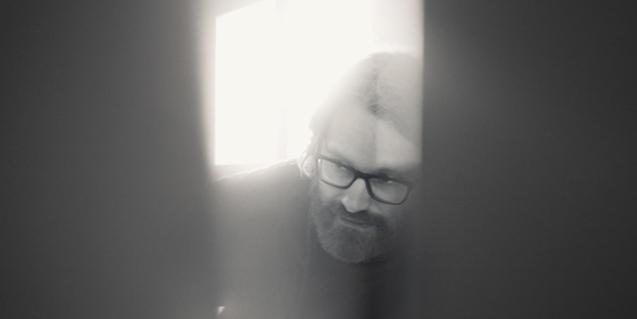 Retrato en blanco y negro del cantante visto a través de un agujero