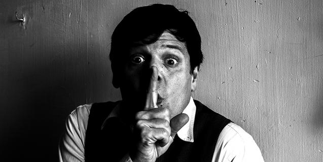 El actor protagonista en un retrato en blanco y negro en el que mira a cámara pidiendo silencio