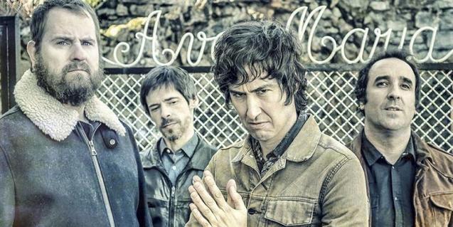 Retrato de grupo de los miembros de la banda mirando a la cámara con gesto serio