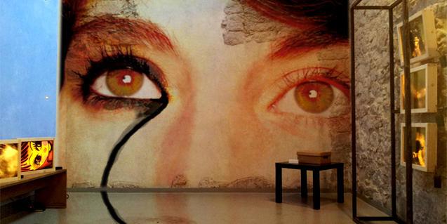 La imatge d'uns ulls de dona de mida gegant, projectada contra un mur