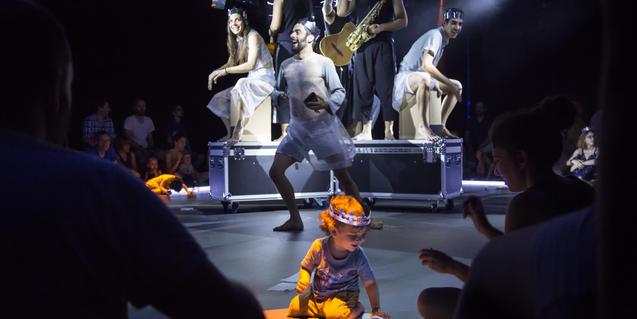Fotografía del espectáculo, un niño en el escenario con los actores y músicos