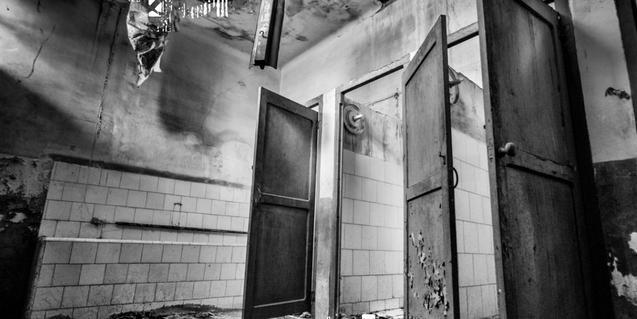 Fotografía en blanco y negro del interior de una antigua fábrica textil abandonada
