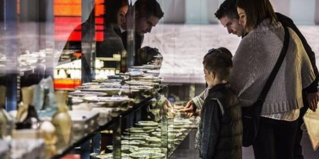 Fotografia d'una família observant una vitrina del museu