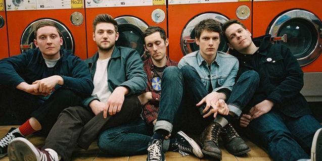 Los miembros de la banda sentados en el suelo y apoyados contra unas máquinas industriales de lavar la ropa