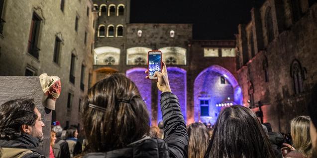Noia filmant concert amb mòbil a la plaça del Rei