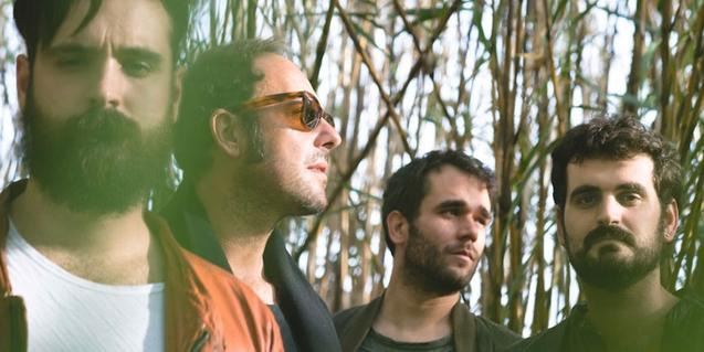 Els quatre integrants de la banda retratats en un bosc