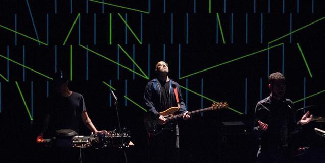 El poeta Eduard Escoffet i els músics de la banda Bradien retratats sobre l'escenari