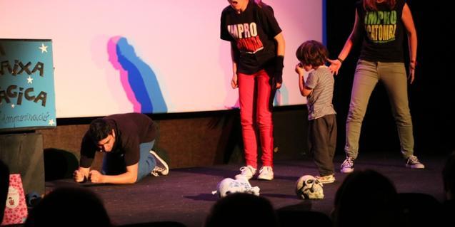 Fotografía de los actores en el escenario con un niño