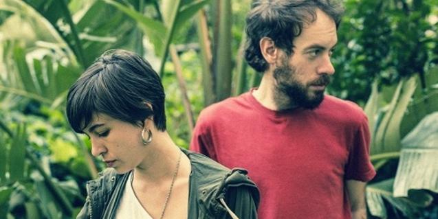 Retrato de los dos integrantes de la banda entre la vegetación y mirando en direcciones opuestas