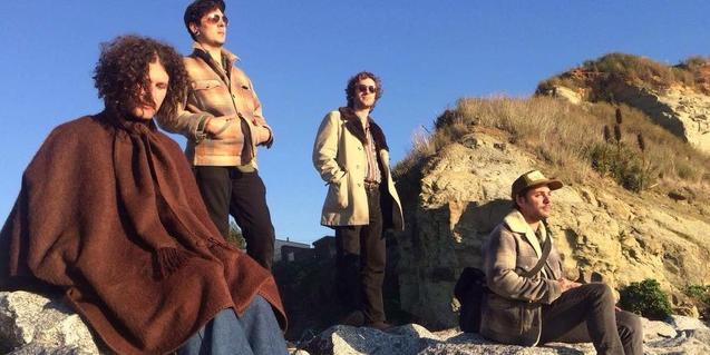 Los integrantes de la banda retratados en exteriores en un paisaje pedregoso