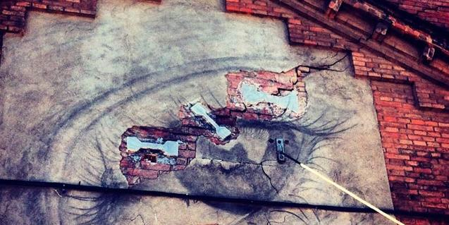 Una fotografía de la artista que muestra una pintada con forma de ojo sobre la pared de un viejo edificio del barrio