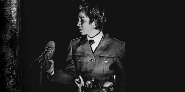 La actriz Celeste Ramos, caracterizada como un dictador militar y con un zapato en la mano