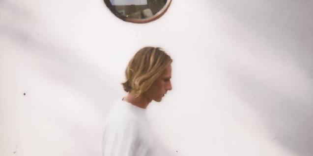Retrat de l'artista vestit de blanc i caminant pel davant d'una paret també blanca