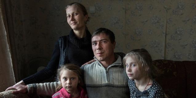 Una família amb un pare una mare i dues filles retratada a casa seva en una zona contaminada per la radiació