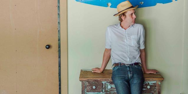 L'artista retratat amb un barret i recolzat contra un moble vell