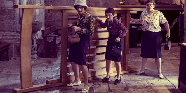 Les tres veïnes porten la cadira arreu.