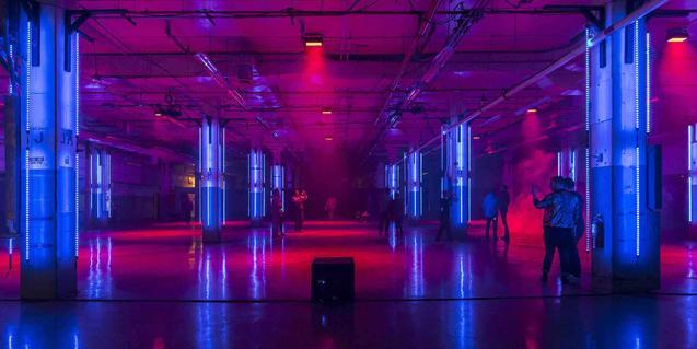 Vista del gran espai d'aspecte industrial que acull la instal·lació audiovisual creada per Playmodes