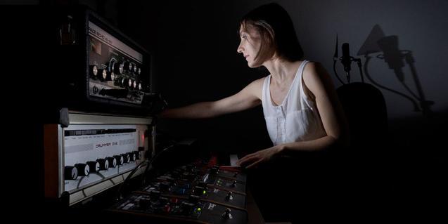 L'artista manipulant els instruments electrònics que fa servir per crear la seva música
